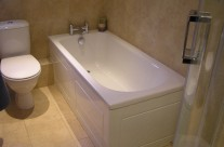 New bath with Nabis Nero taps, solid bath panels and natural tiles